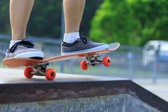 Jambes de planchiste faisant de la planche à roulettes au skatepark Images stock