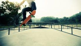 Jambes de planchiste faisant de la planche à roulettes au skatepark Photographie stock