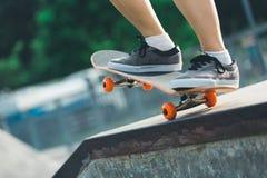 Jambes de planchiste faisant de la planche à roulettes au skatepark Photo stock