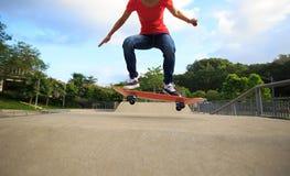 Jambes de planchiste faisant de la planche à roulettes au skatepark Photos stock