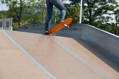Jambes de planchiste faisant de la planche à roulettes sur le skatepark photographie stock