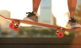 Jambes de planchiste de femme faisant de la planche à roulettes à la ville Photo stock