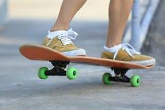 Jambes de planchiste montant la planche à roulettes au skatepark Photo stock
