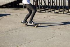 Jambes de planchiste montant la planche à roulettes au skatepark Photographie stock libre de droits