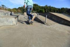 Jambes de planchiste montant la planche à roulettes au skatepark Photographie stock