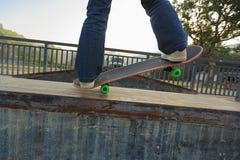 Jambes de planchiste montant la planche à roulettes au skatepark Images libres de droits
