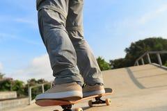 Jambes de planchiste montant la planche à roulettes au skatepark Image stock