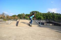 Jambes de planchiste montant la planche à roulettes au skatepark Image libre de droits