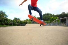 Jambes de planchiste montant la planche à roulettes au skatepark Photo libre de droits