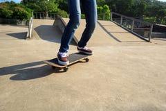Jambes de planchiste montant la planche à roulettes au skatepark Images stock