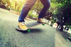 Jambes de planchiste montant la planche à roulettes au skatepark de ville Image libre de droits