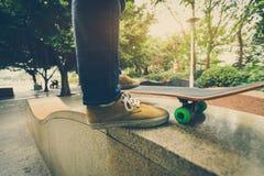 Jambes de planchiste montant la planche à roulettes au skatepark de ville Photos libres de droits