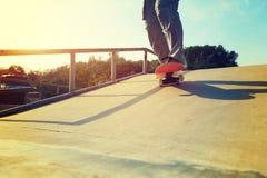 Jambes de planchiste montant la planche à roulettes au skatepark de ville Photo libre de droits