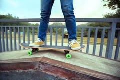 Jambes de planchiste montant la planche à roulettes au skatepark de ville Image stock