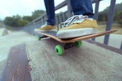 Jambes de planchiste montant la planche à roulettes au skatepark de ville Images libres de droits