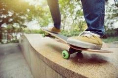 Jambes de planchiste montant la planche à roulettes au skatepark de ville Images stock