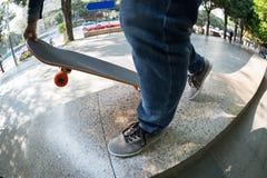Jambes de planchiste montant la planche à roulettes au skatepark de ville Photographie stock