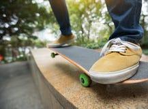 Jambes de planchiste montant la planche à roulettes au skatepark de ville Photographie stock libre de droits
