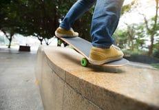 Jambes de planchiste montant la planche à roulettes au skatepark de ville Photo stock
