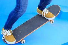 Jambes de planchiste montant la planche à roulettes sur le skatepark Photo stock