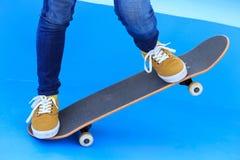 Jambes de planchiste montant la planche à roulettes sur le skatepark Images stock