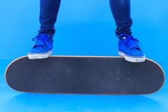 Jambes de planchiste montant la planche à roulettes sur le skatepark Image stock