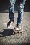 Jambes de planchiste montant la planche à roulettes sur la rue photographie stock libre de droits