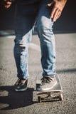 Jambes de planchiste montant la planche à roulettes sur la rue photographie stock