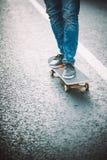 Jambes de planchiste montant la planche à roulettes sur la rue photo stock