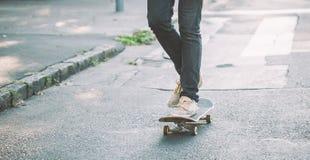 Jambes de planchiste montant la planche à roulettes sur la rue images stock