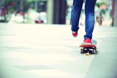 Jambes de planchiste montant sur la planche à roulettes sur la ville Image libre de droits