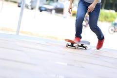 Jambes de planchiste montant sur la planche à roulettes sur la ville Photos libres de droits
