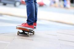 Jambes de planchiste montant sur la planche à roulettes sur la ville Photo stock