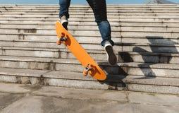 Jambes de planchiste sautant avec la planche à roulettes Photos libres de droits