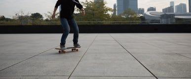 Jambes de planchiste sautant avec la planche à roulettes Image stock