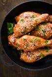 Jambes de poulet épicées cuites au four avec le sésame et le persil dans la poêle de fonte sur le fond en bois foncé photos stock