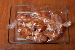 Jambes de poulet avant la cuisson dans un sac à cuisson image libre de droits