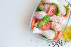Jambes de poulet crues crues, pilon avec des tomates et basilic dedans Photographie stock