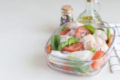 Jambes de poulet crues crues, pilon avec des tomates et basilic dedans Photographie stock libre de droits