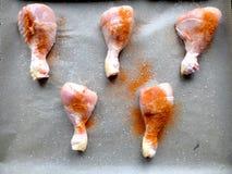 Jambes de poulet crues préparées pour faire cuire dans le four sur la moule et soutenir le papier avec du sel et le poivron rouge image stock