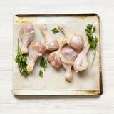 Jambes de poulet crues crues sur un papier de plaque de cuisson sur le plateau au-dessus du fond en bois blanc, vue supérieure Pl photographie stock libre de droits