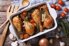 Jambes de poulet cuites au four avec la vue supérieure horizontale en gros plan de légumes Photos stock