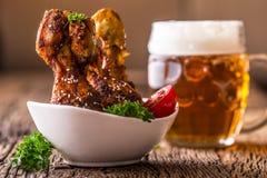 Jambes de poulet de gril BBQ grillé de jambes de poulet avec la tomate de persil de sésame et la bière pression Photographie stock