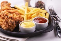 Jambes de poulet et pommes frites croustillantes Nourriture industrielle rapide photos stock