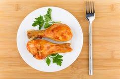 Jambes de poulet frit avec la sauce tomate et le persil dans le plat Images libres de droits