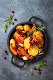 Jambes de poulet rôti avec les légumes à racine, le citron, l'ail, la canneberge et le romarin sur la casserole images stock