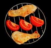 Jambes de poulet sur le gril avec la vue supérieure découpée en tranches de tomate sur le noir Photos stock