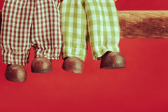 Jambes de poupée en céramique sur le fond rouge Photos stock