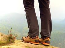 Jambes de randonneur dans les bottes confortables de trekking sur la roche Équipez les jambes dans des pantalons extérieurs léger Photographie stock
