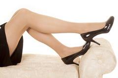 Jambes de robe de noir de femme sur des talons de banc photo libre de droits